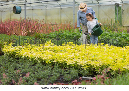 Grandfather and child watering plants - Stock Photo