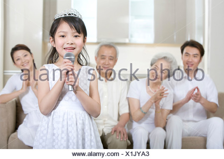Little girl sings in front of her family - Stock Photo