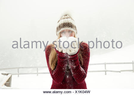 Young woman blowing handful of powder snow - Stock Photo