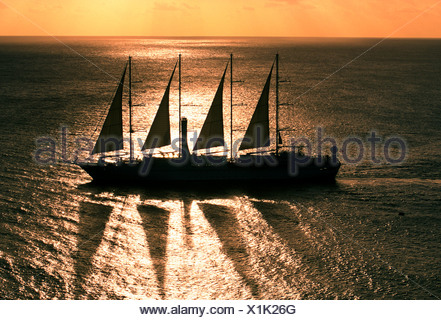 Sailing boat at full mast in sea near St Lucia at sunset - Stock Photo
