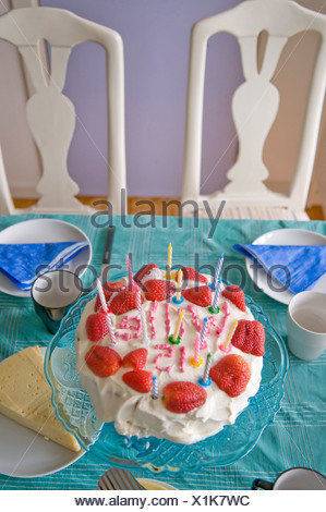 strawberry birthday cake with candles stock photo