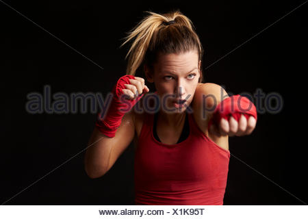 Young blonde woman shadow boxing, throwing a punch - Stock Photo