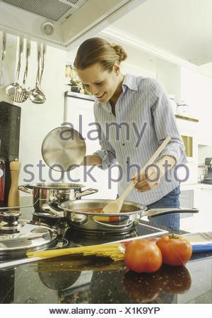 Frau beim Kochen am Herd (model-released) - Stock Photo