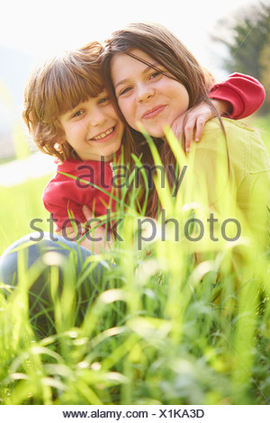 Sister and younger brother sitting in grassy field - Stock Photo