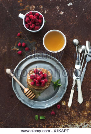 Breakfast set. Buckwheat pancakes with fresh raspberries, honey and mint leaves over grunge metal background, top view, selectiv - Stock Photo
