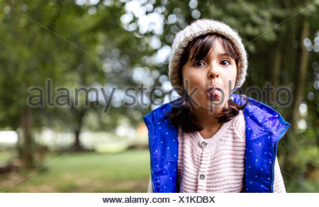 Portrait of little girl sticking out her tongue - Stock Photo