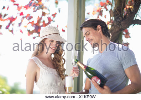 Couple drinking champagne in garden wine bar - Stock Photo