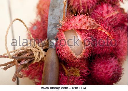fresh tropical rambutan fruits over rustic wood table. - Stock Photo