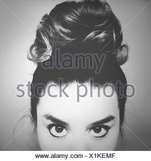 Close-Up Portrait Of Young Woman With Hair Bun - Stock Photo