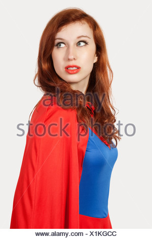 Young woman in superhero costume looking away - Stock Photo