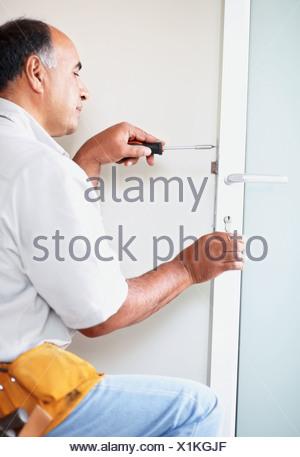 Man Fixing Door   Stock Photo
