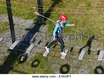 Teenage girl walking on rope bridge - Stock Photo