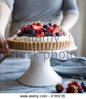 Woman with a No-Bake Lemon Berry Coconut Cream Tart with fresh berries (vegan, gluten-free, refined sugar-free) on a cake stand - Stock Photo