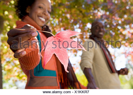 Couple walking hand in hand in autumn park focus on woman holding red maple leaf smiling side view portrait - Stock Photo