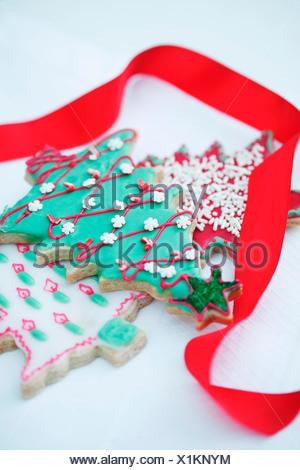 A decorated biscuit in the shape of a Christmas tree, and a red gift ribbon - Stock Photo