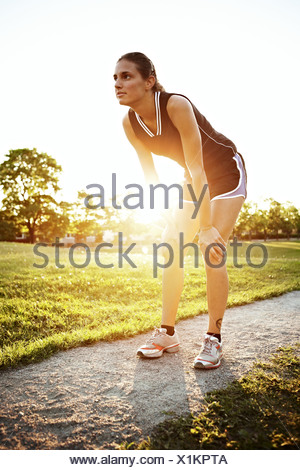 Young woman doing stretching exercises outdoors, Sweden. - Stock Photo