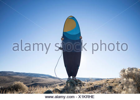 Man holding a surfboard in the desert, Wyoming, America, USA - Stock Photo