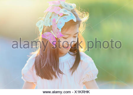 Girl (8-9) with butterflies in hair - Stock Photo