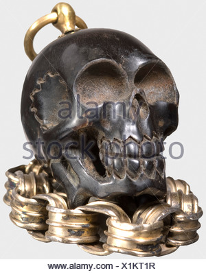 A German miniature memento-mori skull, 17th century A small, delicately carved skull of dark horn. There is a fire-gilded brass suspension ring mounted at the top of the skull, attached to a contoured, gilt silver belcher chain. Height without ring 3.5 cm. Length of the chain 14 cm. historic, historical,, 17th century, handicrafts, handcraft, craft, object, objects, stills, clipping, clippings, cut out, cut-out, cut-outs, jewellery, jewelry, noble, precious, - Stock Photo