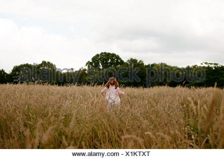 A little girl walking in a field, rear view - Stock Photo