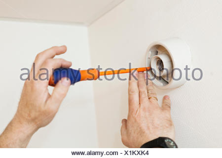 Cropped image of electrician's hands using screwdriver on bulb socket - Stock Photo