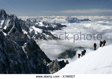 Mountaineers and climbers hiking on a snowy ridge, Aiguille du Midi, Mont Blanc Massif, Chamonix, French Alps, Haute Savoie, France - Stock Photo