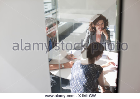 Business people meeting in sunny conference room - Stock Photo