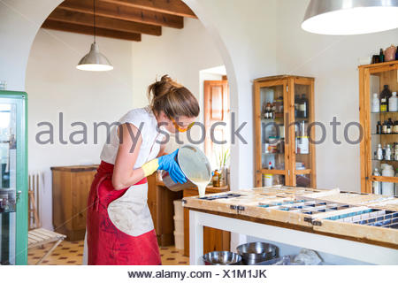 Young woman pouring liquid lavender soap into moulds in handmade soap workshop - Stock Photo