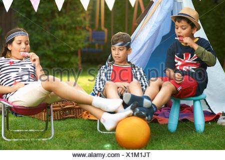 Girl and brothers eating ice lollies in front of homemade tent in garden - Stock Photo
