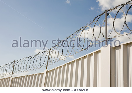 Barbed wire and a fence - Stock Photo