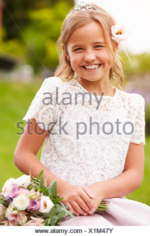 Outdoor Portrait Of Bridesmaid Holding Bouquet - Stock Photo