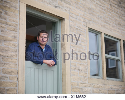 Portrait of farmer looking out from farmhouse door - Stock Photo