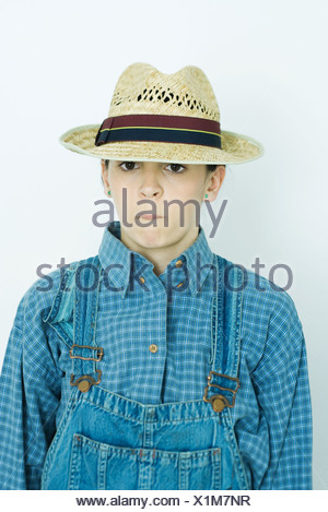 Teen girl wearing overalls and cap, making face, portrait - Stock Photo