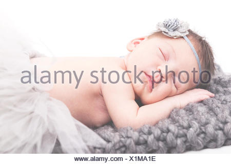 Portrait of a newborn baby girl sleeping on blanket - Stock Photo