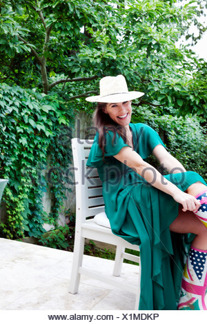 Young woman wearing green dress and hat sitting on chair in garden