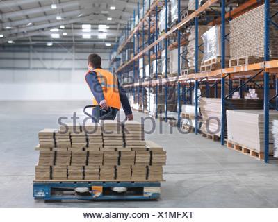 Worker Transporting Load In Warehouse - Stock Photo