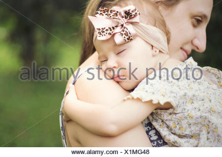 Close-Up Side View Of A Mother Carrying Baby Outdoors - Stock Photo