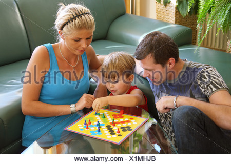 young family sitting in front of a davenport, playing a board game - Stock Photo