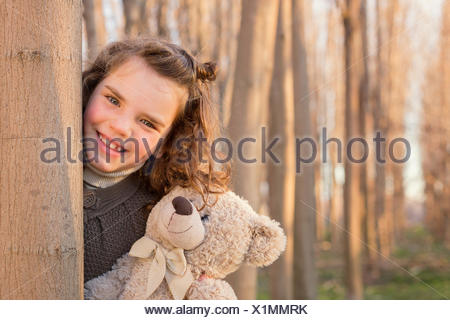 Girl hiding behind tree trunk with her teddy bear - Stock Photo