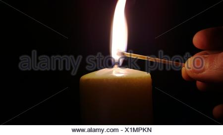 Man lighting a candle with a match - Stock Photo