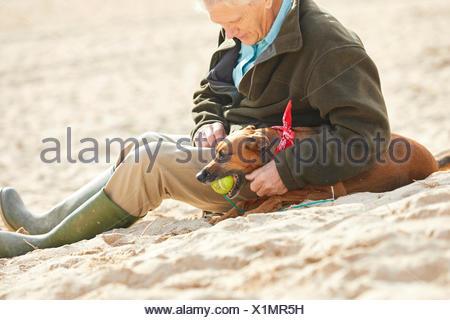 Man and dog sitting on beach, Constantine Bay, Cornwall, UK - Stock Photo