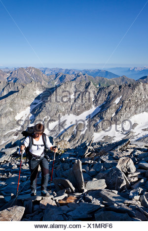 Female mountaineer climbing Hochfeiler mountain, Pfitschertal, Eisack and Wipptal valleys, and the Dolomites at the back - Stock Photo