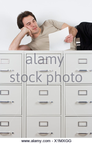 Man reading lying atop file cabinets - Stock Photo