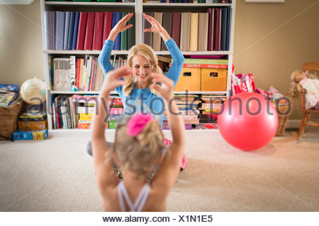 Mother and young daughter practicing ballet in sitting room - Stock Photo
