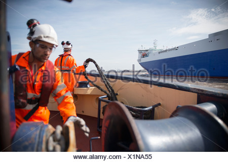 Workers on tug boat reeling in rope - Stock Photo