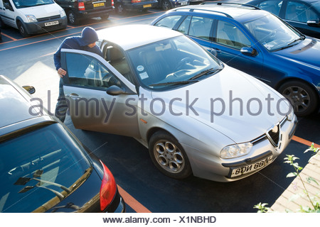 A thief breaking into a car - Stock Photo