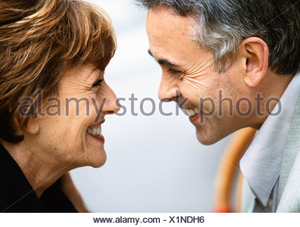 Mature man and woman looking at each other smiling, close up - Stock Photo