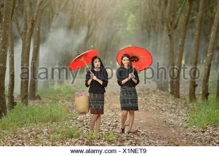 Two women walking along rural footpath, Thailand - Stock Photo