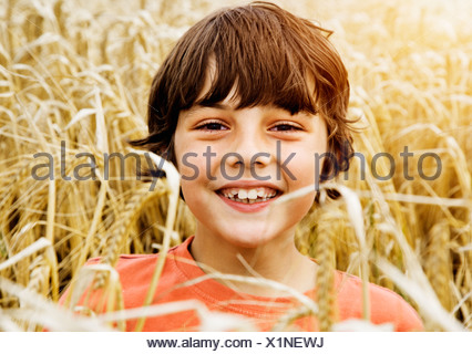 Boy smiling in wheat field - Stock Photo
