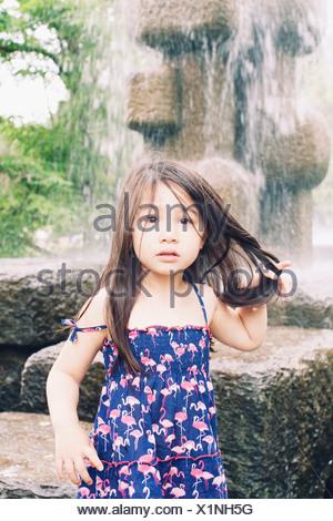 Little girl by water fountain, portrait - Stock Photo